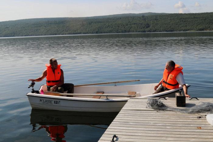 Bilde av båt og to fiskere